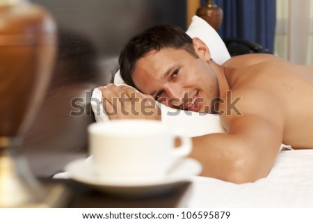 man sleeping on a bed, a cup of tea on the bedside table and lamp