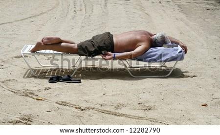 man sleeping on lounge chair on beach