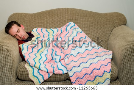 Man sleeping on the couch because he is feeling ill, or maybe he got in trouble with his wife