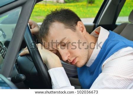 Man sleeps in a car.