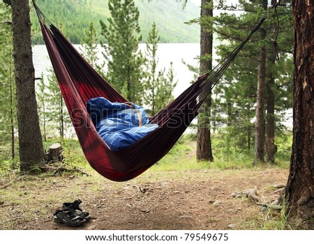 Man sleeps in a hammock and in a sleeping bag early in the morning
