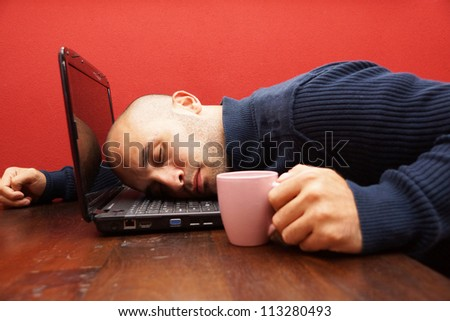 Man sleeps in front of his laptop