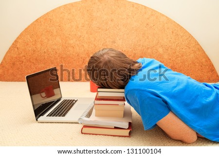Man sleeps in front of his laptop on pile of books
