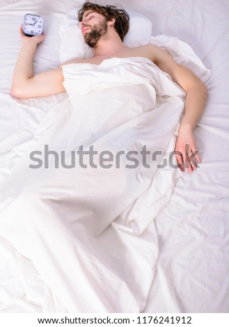 Man sleepy drowsy unshaven bearded face covered with blanket having rest. Guy lay under white bedclothes. Fresh bedclothes concept. Turn off alarm clock. Man unshaven relaxing bed hold alarm clock. #1176241912