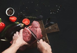 Man slicing filet mignon on wooden board at restaurant kitchen. Chef preparing fresh meat for cooking. Modern cuisine backgroung with herbs and vegetables, copy space, top view