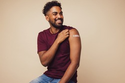 Man smiling after receiving vaccination. Man showing his arm after receiving a vaccine.