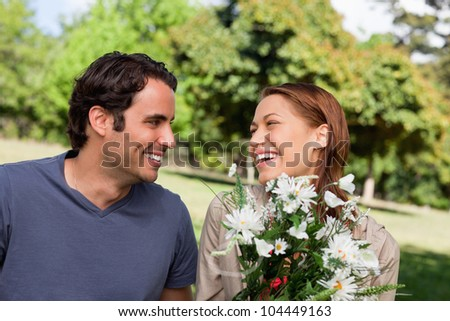 Man smiling as he watches his friend laughing while holding a bunch of flowers while sitting in a bright park