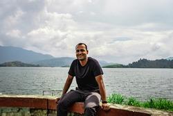 man smiling at pristine lake with mountain background image is taken at banasura sagar dam wayanad kerala india. the natural beauty of this place is amazing.