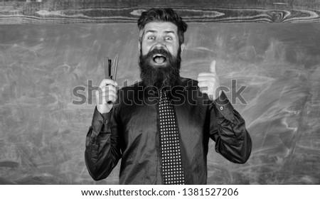 Man smiling hold stapler stationery. Teacher bearded man with stapler chalkboard background. Prepare for school season buy stationery. Hipster teacher formal necktie holds stapler. School stationery.