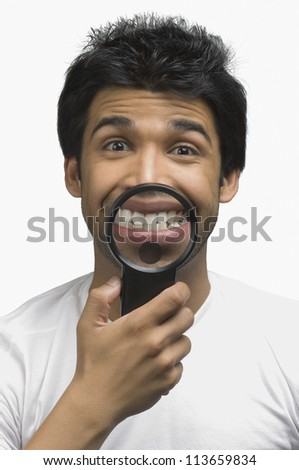 Man smiling in front of a magnifying glass