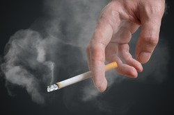 Man (smoker) is holding cigarette in hand on black background. Smoke around.
