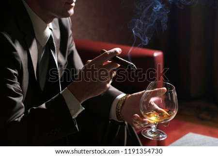 Man smokes cigar and a glass of wine in his hand