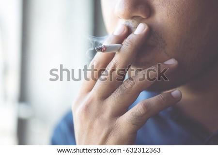 man smoking a cigarette. Cigarette smoke spread.