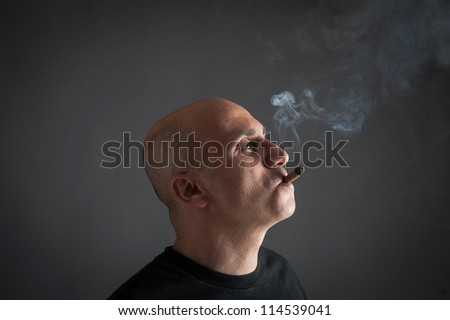 Man smoking cigar portrait on dark background.