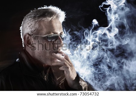 Man smoking cigarette at night, closeup.