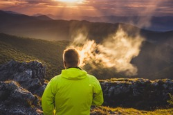 Man smoking cigarette - dust in the air, sunrise nature scenery