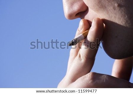man smoking cigarette on sky background