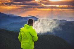 Man smoking cigarette sunset in mountain