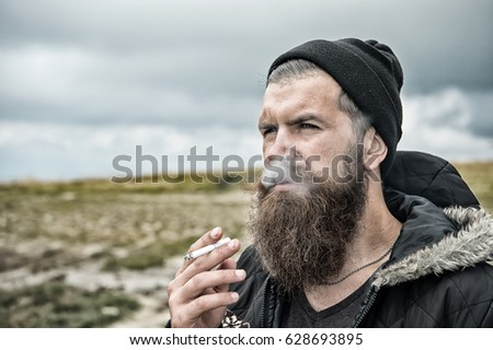 man smoking cigarette, young bearded hipster in hat and jacket at mountain and cloudy sky on natural background, copy space