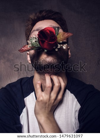 man smothering his feelings - toxic emotions - love disappointment -  young guy with a rose in his mouth #1479631097