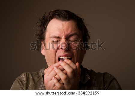 Man sneezing due to having a cold
