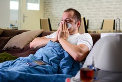 Man sneezing into a tissue. Young ill man uses tissue paper sneezing. Flu, cold concept. minimize risk of viral transmission. Staying at home can help stop coronavirus spreading concept.