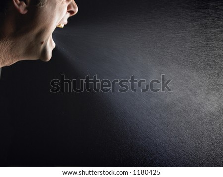 Man sneezing over black background - stock photo