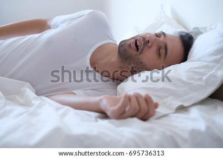 Man snoring because of sleep apnea lying in the bed Foto stock ©