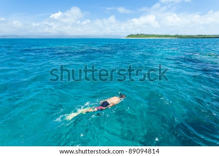 Man snorkeling over coral reef with clear blue tropical water, Okinawa, Japan