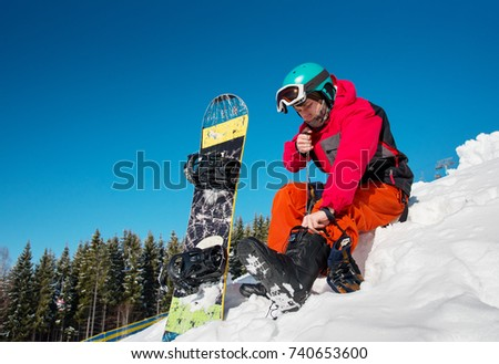 Man snowboarder sitting on the snow, preparing for riding the slope at ski resort in the mountains. copyspace relax rest recreation winter sports activity hobby leisure concept #740653600