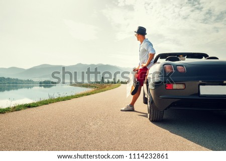Man solo traveler on cabriolet car rest on picturesque mountain road