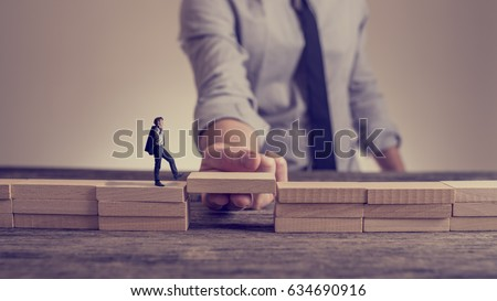 Man solving problems by building bridge with wooden block to span a gap for little businessman walking across in a conceptual retro toned image.
