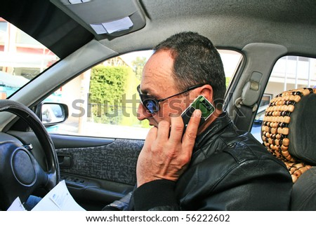 Man speaking by phone in car with business papers.