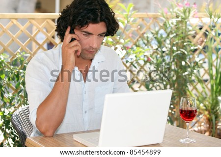 Man speaking on his mobile phone while drinking wine and surfing the Net on a terrace