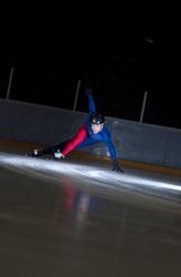Man speed skating in sharp turn