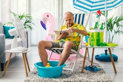 Man spending his summer vacations at home, he is sitting on a deckchair in the living room and reading a book