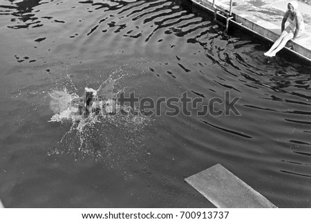 man splashing into swimming pool