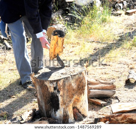 Man splitting logs outside to burn as firewood.