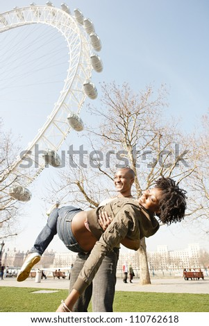 Man spontaneously carrying girlfriend in his arms while visiting London city, with the London Eye and a blue sky in the background.