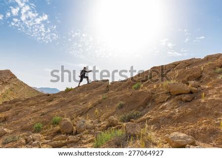 Man sport running ascending desert mountain slope. #277064927