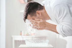 Man spraying water on his face after shaving in bathroom