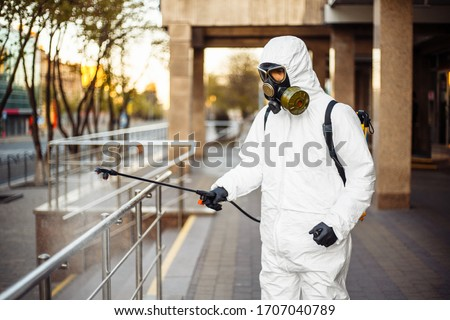 Man sprays disinfector onto the railing wearing coronavirus protective suit and equipment. Cleaning and sterilizing the not crowded city streets. Covid-19 nCov2019 spread prevention Foto stock ©