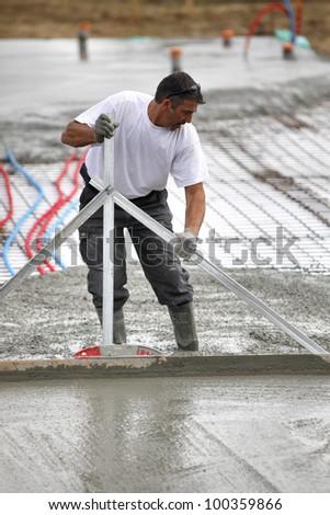 Man spreading wet cement #100359866