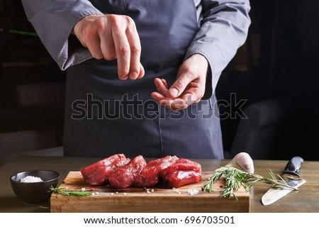 Shutterstock Man sprinkles filet mignon steaks with pepper salt. Chef working at open restaurant kitchen. Fresh meat, garlic and rosemary on wooden board. Modern restaurant cuisine backgroung