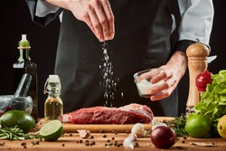 Man sprinkles salt over meat. Chef cooking a beef steak, seasoning with pepper, lime, olive oil, garlic and onion.