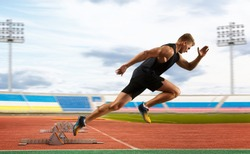 Man sprinter leaving starting blocks on the athletic track