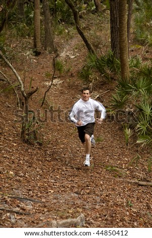 man sprinting on trail in forest