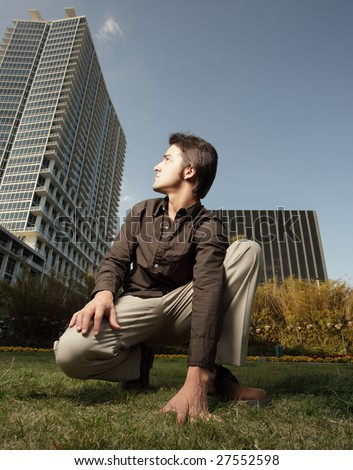 Man squatting and looking back at a tall building
