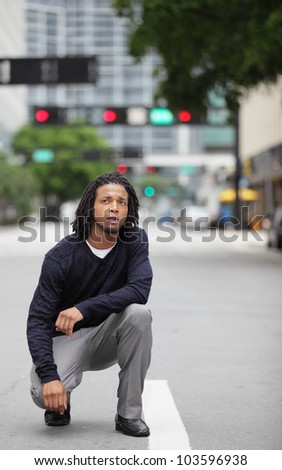 Man squatting in the middle of the street