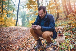 Man Squatting Next To small yellow Dog and using phone in autumn forest